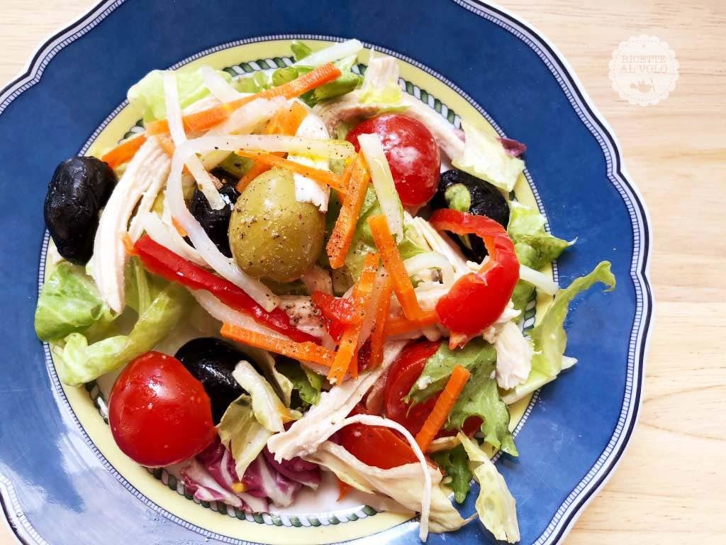 piatto blu con insalata di pollo e olive